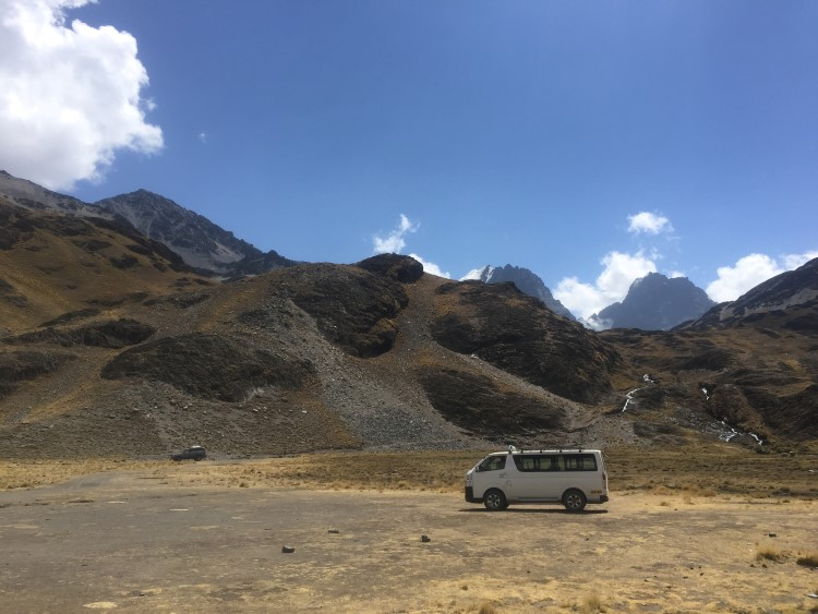 A mini bus in stark Andean scenery in Bolivia, just one of the transport options available to tourists travelling in Bolivia.