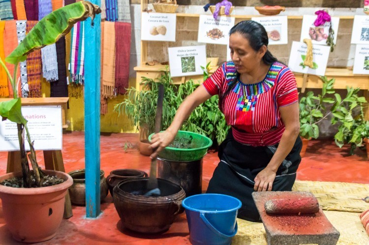 A Mayan woman in a weaving cooperative in San Juan La Laguna dyes yarn using organic dye