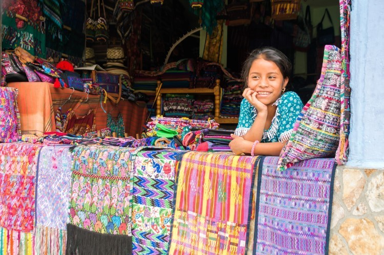 A local girl poses for photographs outside her family's shop in the indigenous community of Santa Catarina Paolopo