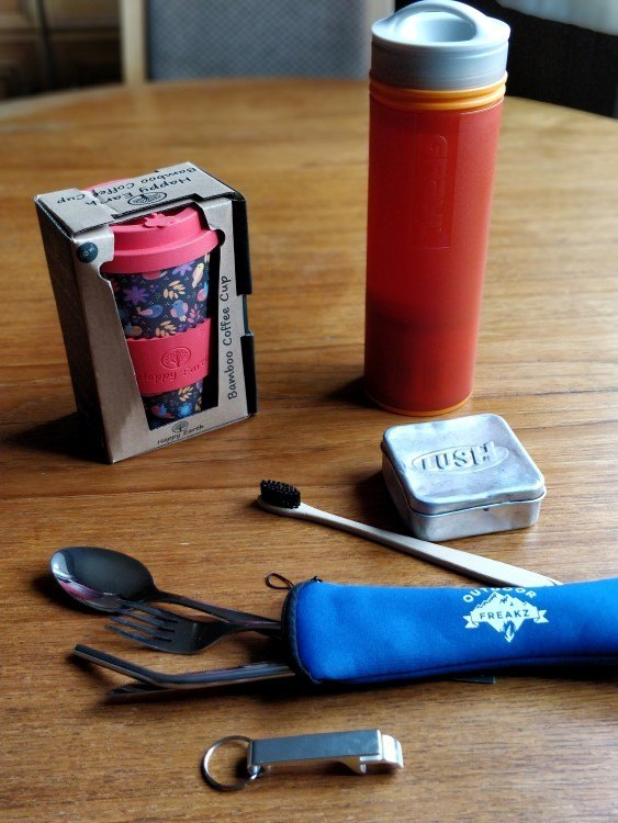 Essentials for eco travel, including a portable cutlery set, backpacking water filter, bamboo mug, bamboo toothbrush and hard conditioner.