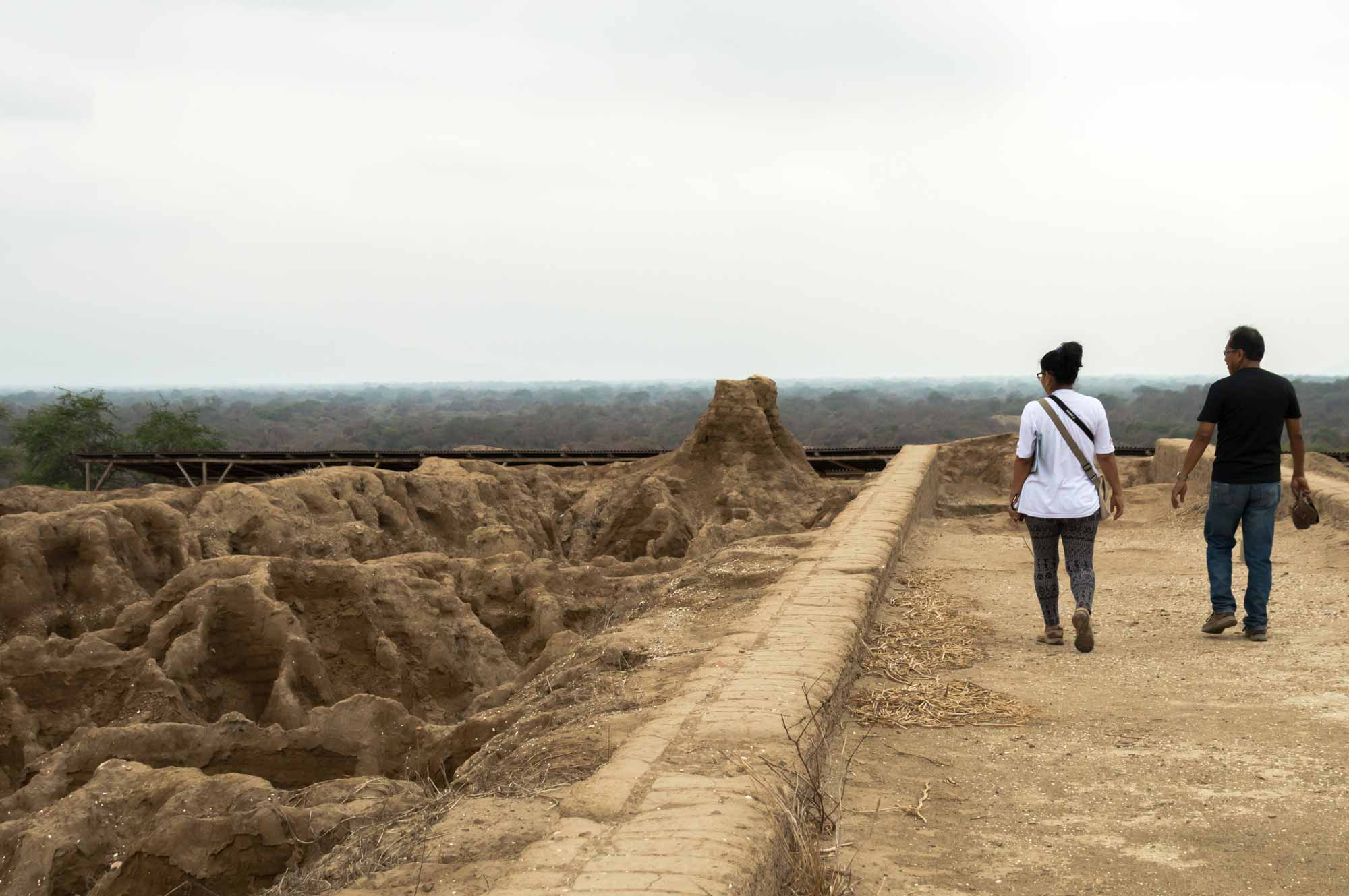 Two people walk on the walls of the Huaca Las Ventanas in what is now the Santuario Historico Bosque de Pomac in northern Peru.