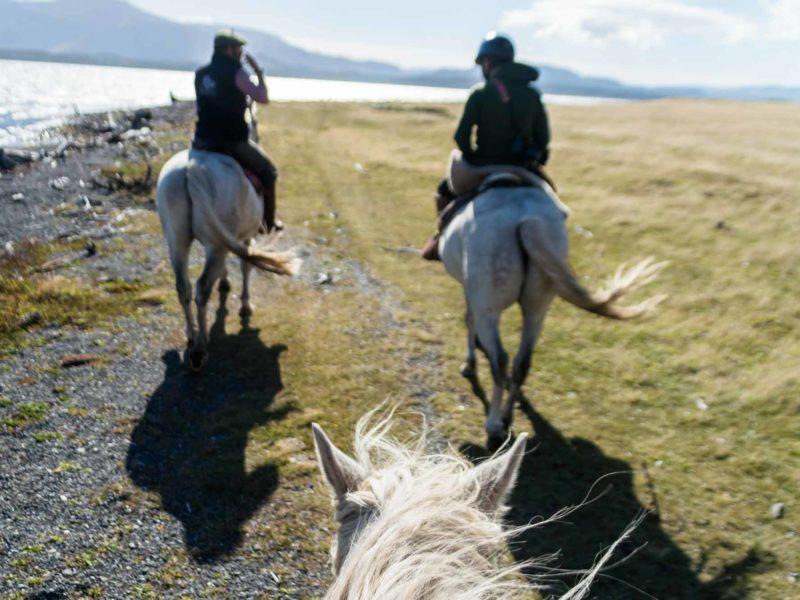 Two horses and riders on Seno Ultima Esperanza at Estancia La Peninsula in Chilean Patagonia