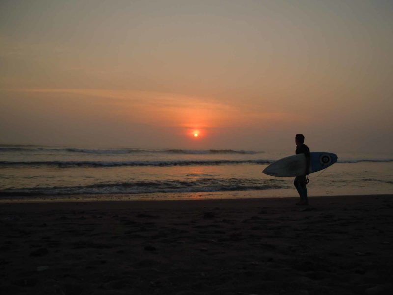 A surfer at sunset on Huanchaco beach near Trujillo in Peru