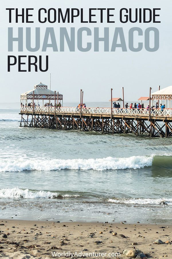 The Huanchaco pier filled with walking tourists extends out over the ocean