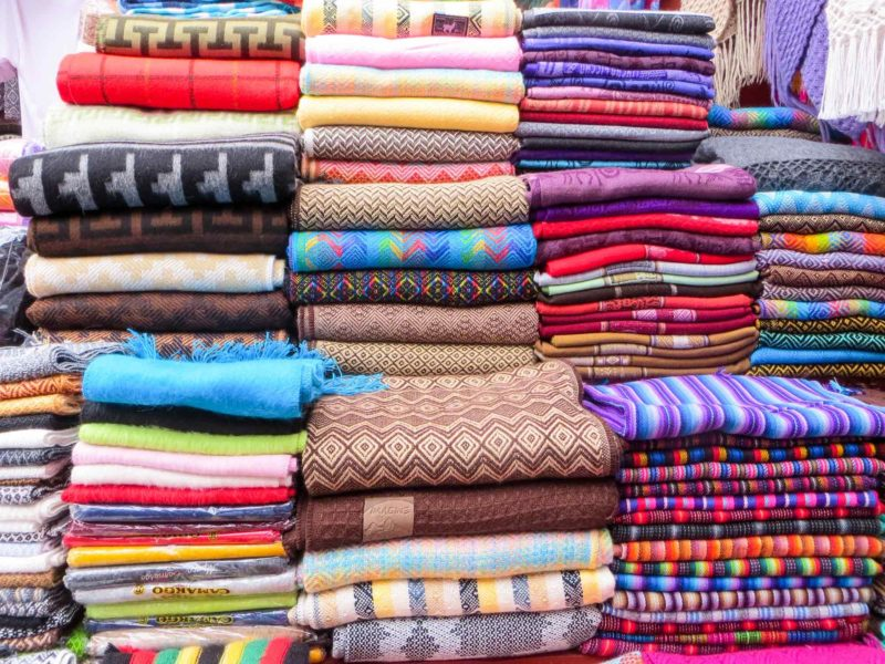 Hand-woven textiles in the market of Pisac in the Sacred Valley and an unmissable place to visit in Peru