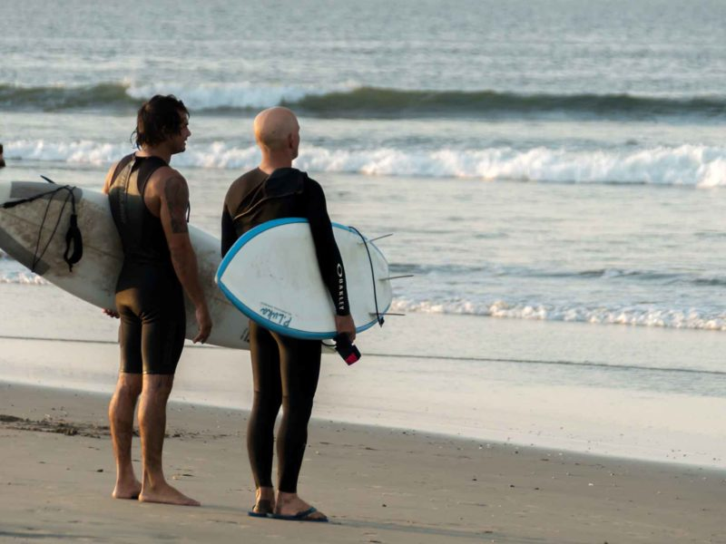 Two men survey the waves at surfing hot spot Lobitos one of the top places to visit in northern Peru