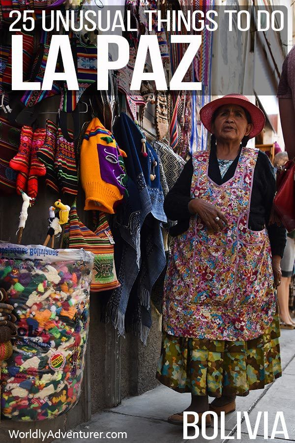 A stall within the clothes markets in La Paz with a local woman wearing a colourful hat and pinafore standing in front of her wares