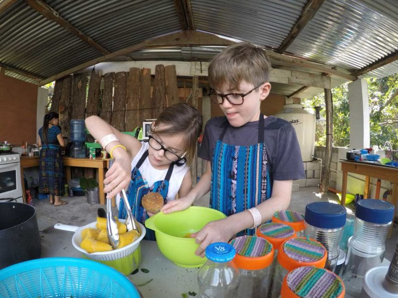 Two children move plantain from a strainer into a bowl as part of a cooking class in San Pedro la Laguna, one of the unmissable things to do in Guatemala