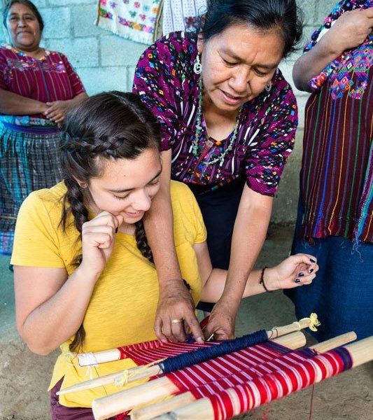 Learning how to weave in the textile cooperative of Santo Domingo Xenacoj, a workshop you can take can visit on a women travel group tour