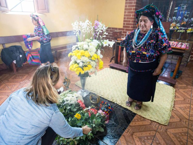 Presenting flowers in a shrine in the town of Santo Domingo Xenacoj in Guatemala, an experience you can have can visit on a women travel group tour