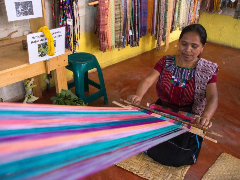 A woman weaves in the community of San Juan la Laguna where they dye textiles using organic dyes, a workshop you can take can visit on a women travel group tour