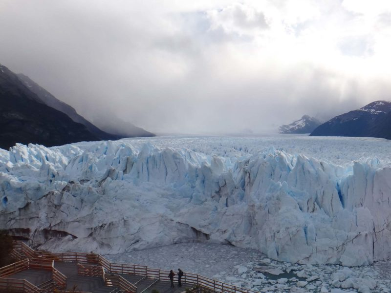 People stand on the wooden walkways in front of the snout of the Perito Moreno Glacier in Patagonia, Argentina