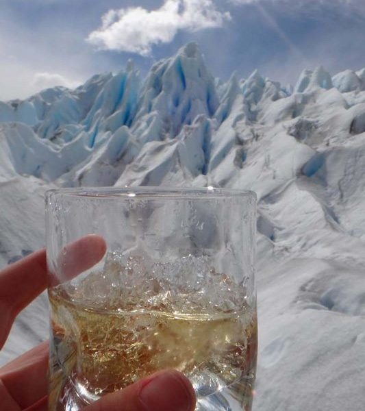 A whisky with ice taken from El Perito Moreno Glacier being held up in front of the glacier itself