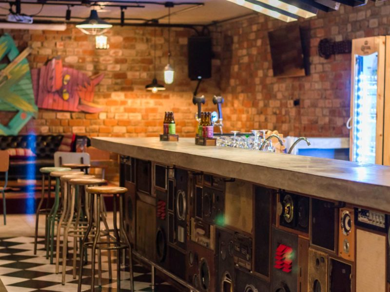 The bar made of speakers and a concrete slab in the underground space at Selina, Lima
