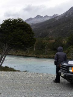 A person stands by a rental car along the Carretera Austral