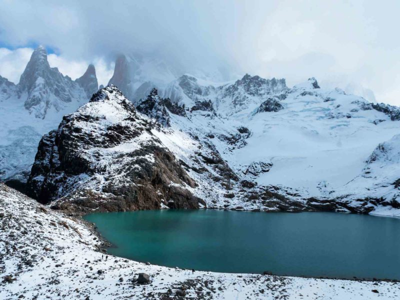 Snowy mountains surround a turquoise blue lake in the Parque Nacional Los Glaciares, Argentina. The best trek through this South American park.