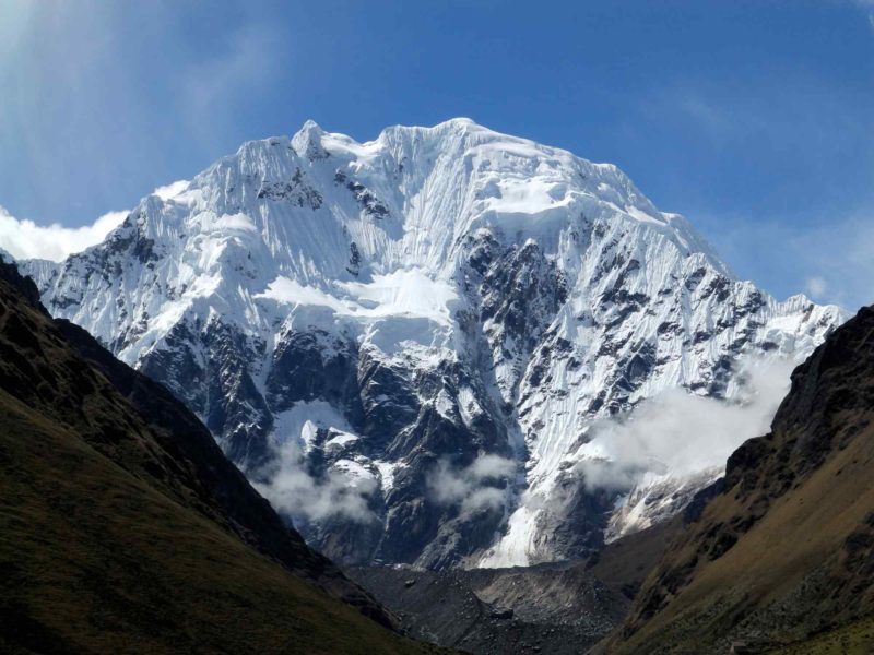 The snow covered peaks of Salkantay peer out from behind grassy lower slopes. Peru is considered one of the best places to hike in South America.