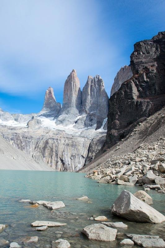 The jagged mountain peaks of the Torres del Paine overlook a glacial lake in Chile. This mountain offers some of the best hiking in South America.