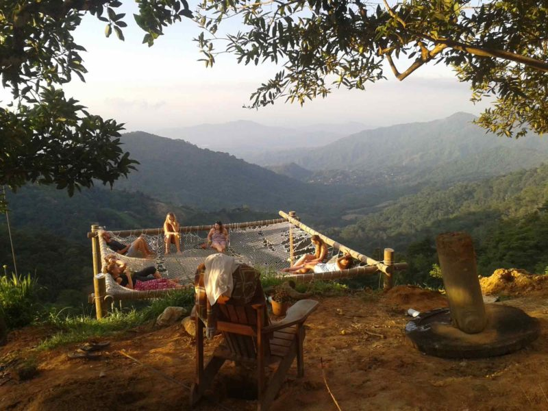 Fellow travelers hang out in a group hammock overhanging the valley in Minca Colombia on these South America Backpacking Routes