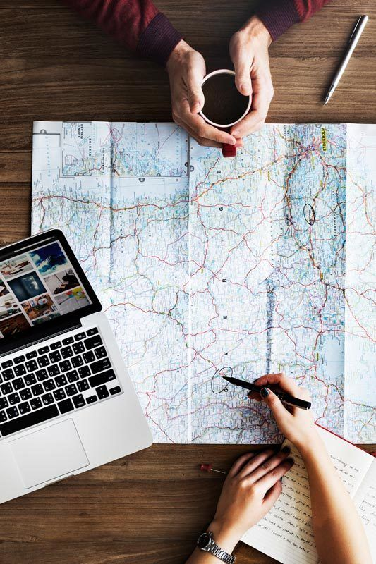A map, notebook and computer as someone plans an itinerary for South America