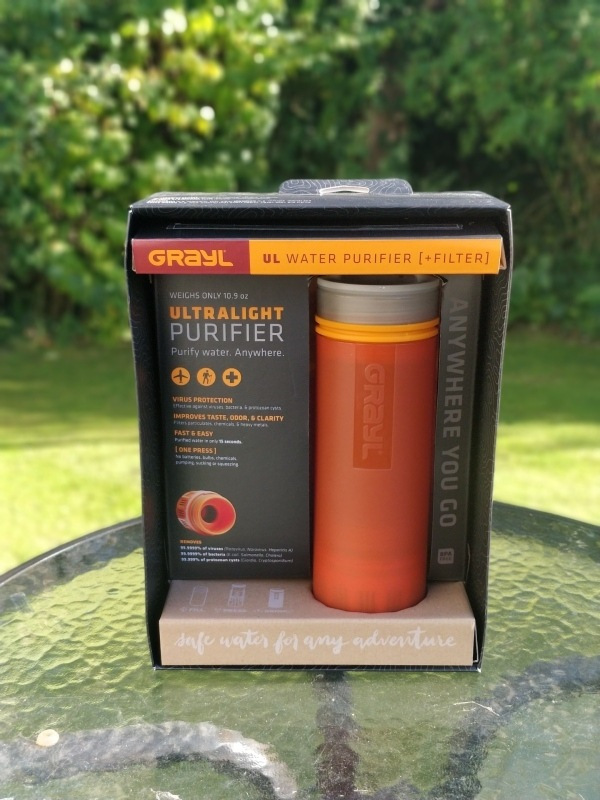 An orange Grayl Geopress travel water filter in its packaging in a natural setting