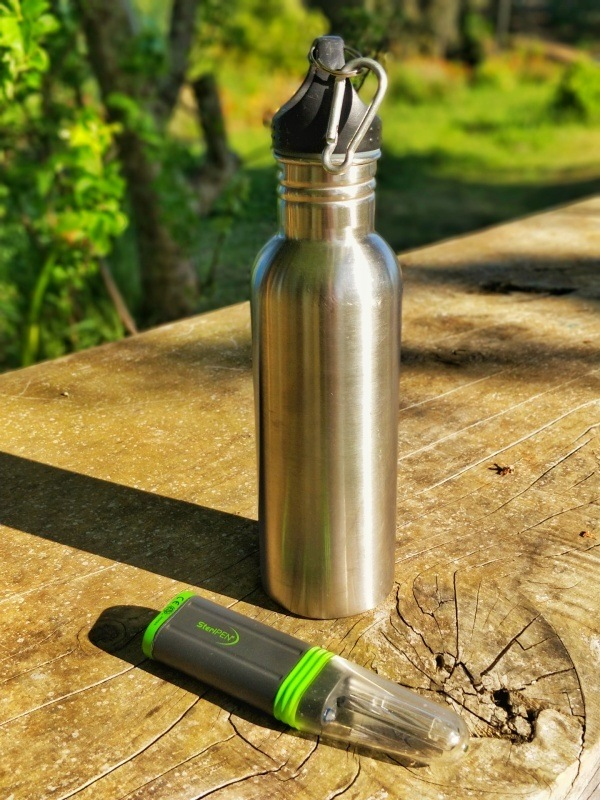 A Steripen water purifier sits next to a silver metal water bottle on a rustic table