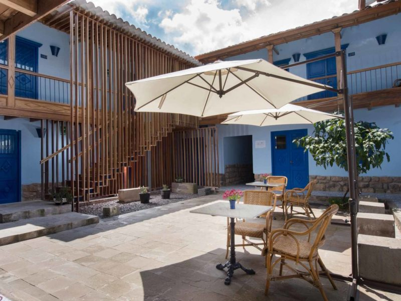 The interior patio of this boutique hotel is surrounded by light blue walls and natural wood balconies