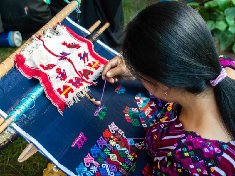 A young girl leans over a weaving in Santo Domingo Xenacoj, a town you can visit on a Guatemala itinerary