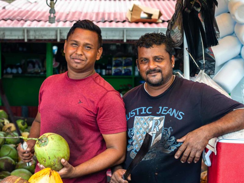 Two men stand in front of their coconut stand in Bourda Market, Guyana in South America