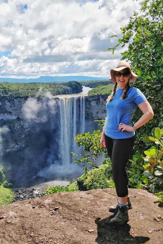 Steph Dyson of Worldly Adventurer posing in front of Kaieteur Falls, one of the world's highest waterfalls located in Guyana, South America