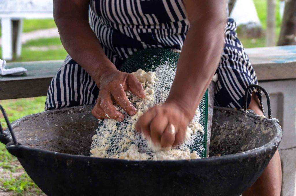 A woman grates raw cassava in Guyana, South America