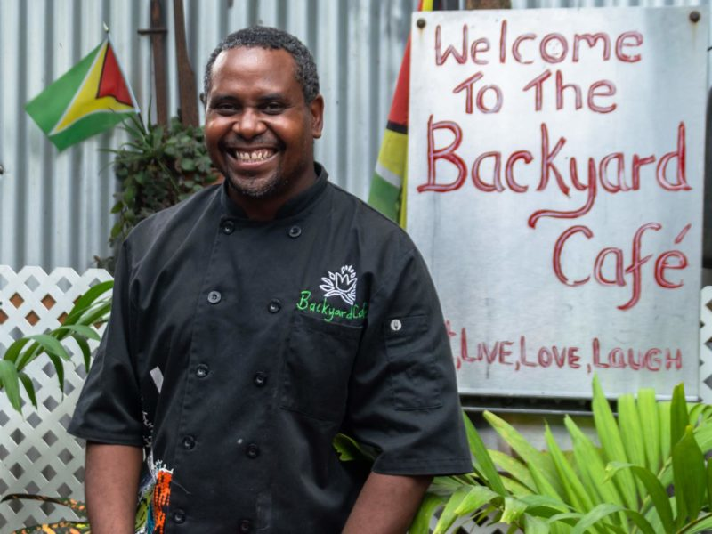 A man smiles in front of a sign for the Backyard Cafe in Guyana.