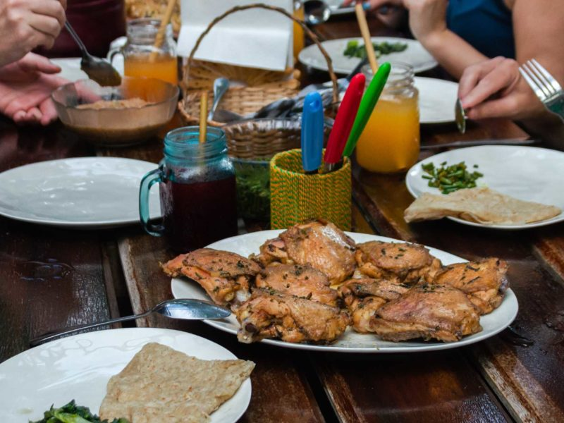 Tourists in Guyana gather around a rustic table and chat over pieces of chicken.