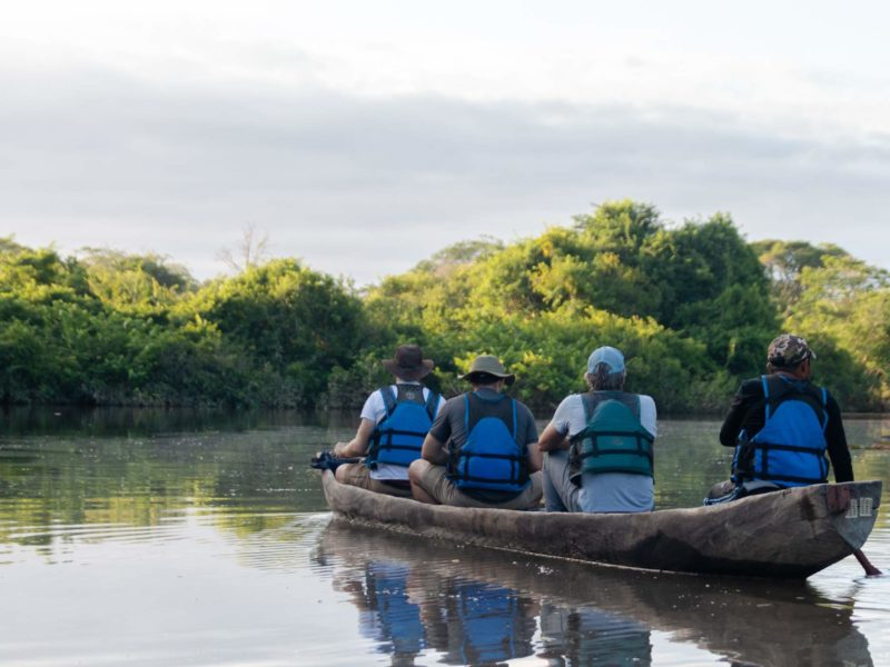 Four people in a dugout canoe paddle over a lake.