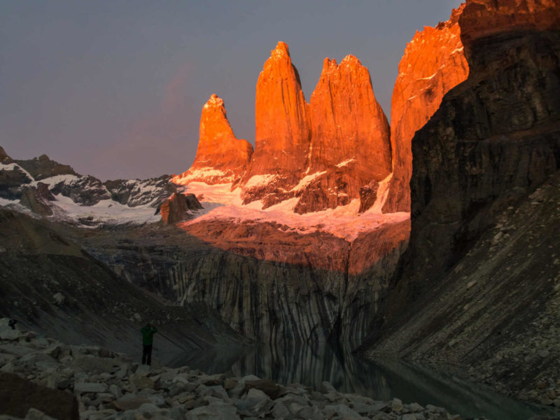 The towers of Torres del Paine lit up in orange at Lago Torres in Torres del Paine National Park, Patagonia