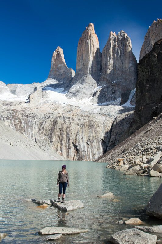 A person stands on a rock in the lake in front of the towers or torres of Torres del Paine National Park, a viewpoint accessible on a day hike in the park