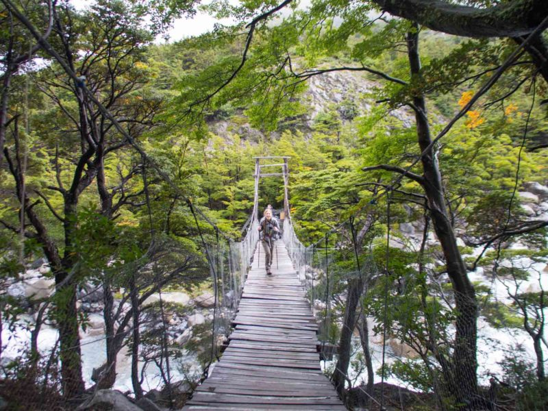 A hiker on a rope bridge to Valle Frances in Torres del Paine National Park, a place for day hikes in Patagonia