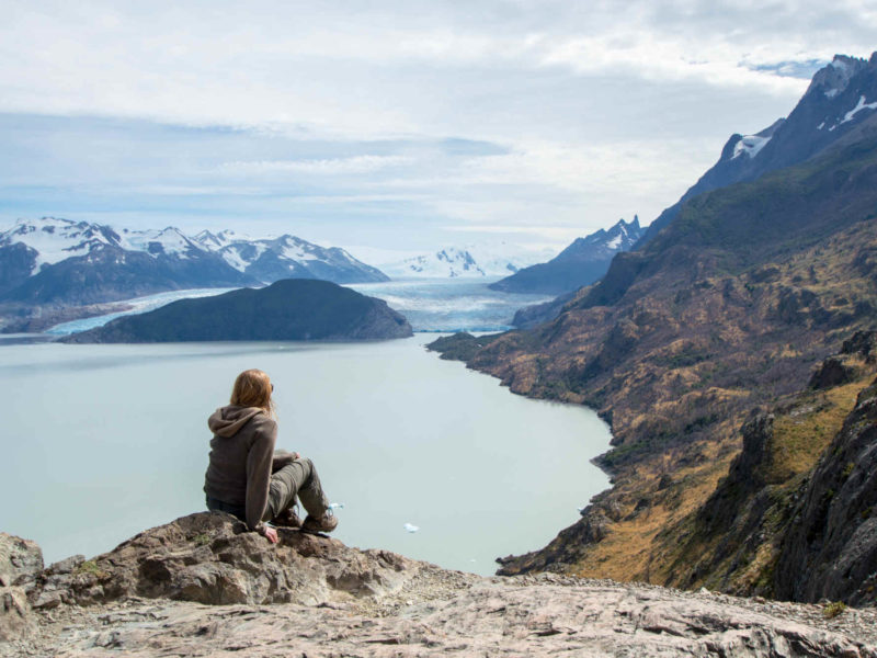 A hiker sits on a rock at the Quebrada de los Vientos (Windy Gorge) viewpoint in Torres del Paine National Park with Lago Grey and Glaciar Grey in the background