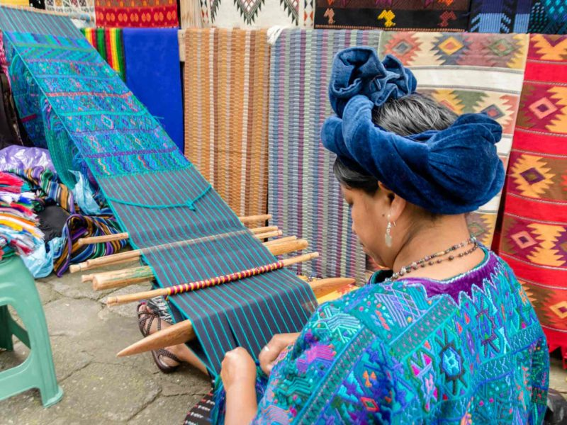 A woman weaves at a loom in Panajachel, an unmissable destination on a guatemala itinerary