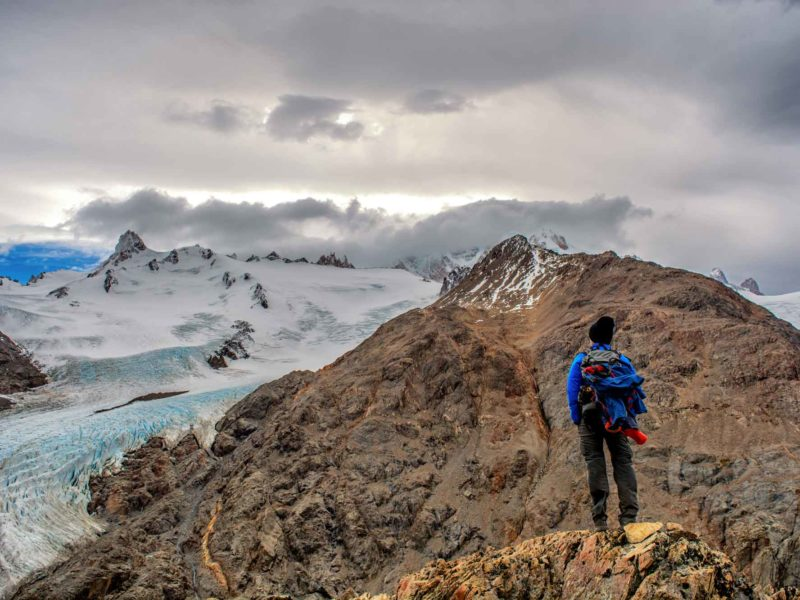 A man stands on a rock overlooking the Southern Patagonian Ice Field on the Huemul Circuit in Argentine Patagonia