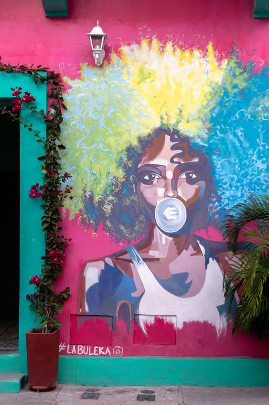 A Black afro-Caribbean woman with a rainbow-coloured afro blows bubble gum on a piece of street art in Cartagena, Colombia