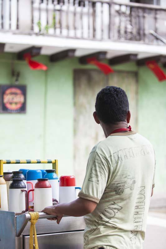 A tinto seller or coffee seller stands by his cart in Cartagena, Colombia