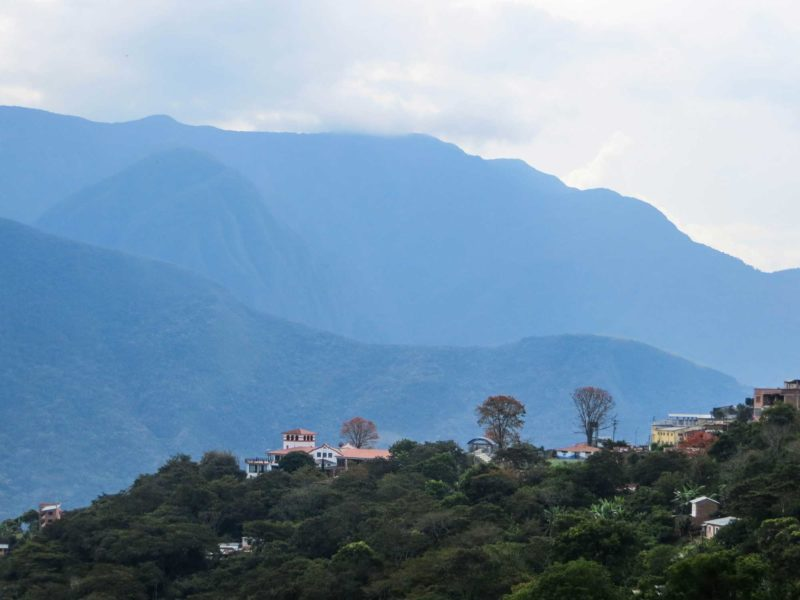 Buildings in the village of Coroico on a vegetated ridge with high mountains behind