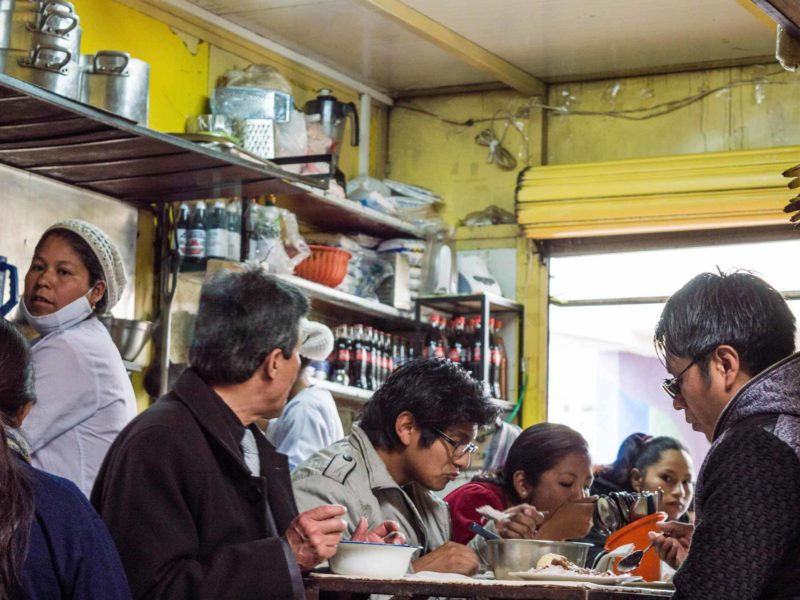 Local pacenos eat lunch at a market stall in La Paz, Bolivia