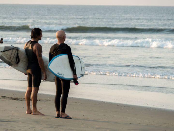Surfers stare at the ocean from the beach in Lobitos on Peru's northern coast